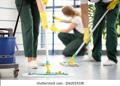 Coworkers moping the floor and a woman dusting a railing in an office