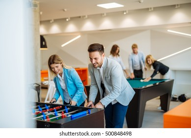 Coworkers playing a foosball table in an office.