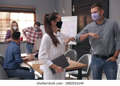 Coworkers with protective masks making elbow bump in office. Informal greeting during COVID-19 pandemic