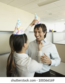 Co-workers putting on party hats at office party