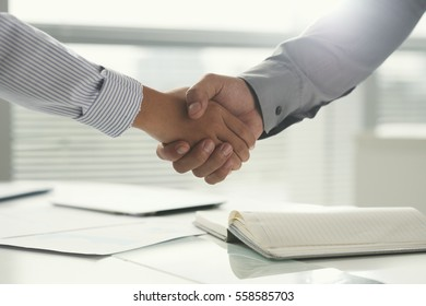 Coworkers shaking hands after successful meeting