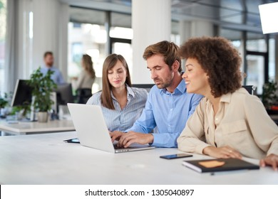 Coworkers sitting at table and solving problem. Man using laptop while two female colleagues looking at laptop and helping him.