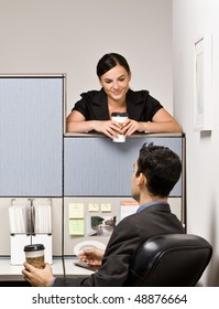 Co-workers talking in office cubicle