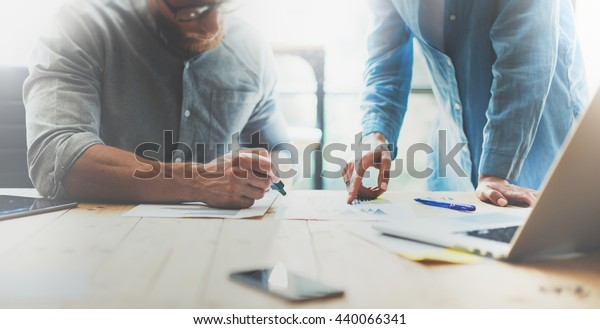 Coworkers team brainstorming process in modern office.Project manager wearing glasses,man makes notes marker.Young business crew working with startup studio.Laptop wood table.Blurred,film effect.Wide