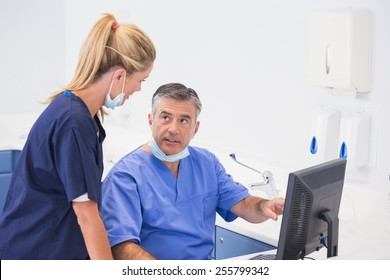 Co-workers using computer and talking in dental clinic