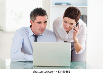 Coworkers working with a laptop and a cellphone in an office