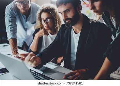 Coworkers working together in modern office.Bearded man talking with colleague and using laptop while sitting at the wooden table.Horizontal.Blurred background