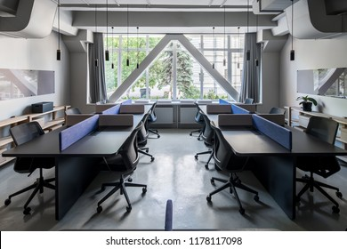 Coworking in a loft style with gray walls and glossy floor. There are black tables with partitions, dark chairs, wooden shelves with boxes and plant, boards, windows with curtains, hanging lamps.