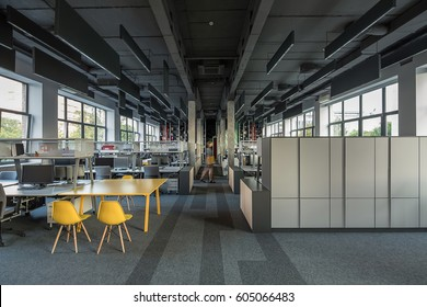 Coworking in a loft style with large windows, gray walls, concrete columns and a carpet on the floor. There are many workplaces with computers and metal reticulated shelves and lockers. Horizontal.