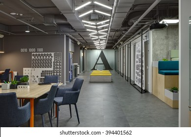 Coworking in a loft style. On the left there are tables with orange legs and blue chairs. On the table there are plants in the pots, pen holders, brick and a folder. Further to the left there is a