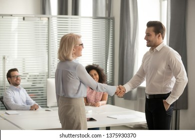 In coworking shared room sitting diverse corporate millennial staff looking at middle aged lady boss welcoming new worker, praising best employee, greeting company client with handshake express regard