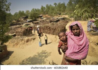 COX' BAZAR, BANGLADESH - MARCH 16, 2017 : Rohingya woman carrying her child in rohingya Kutupalong refugee camp near Cox's Bazar, Bangladesh