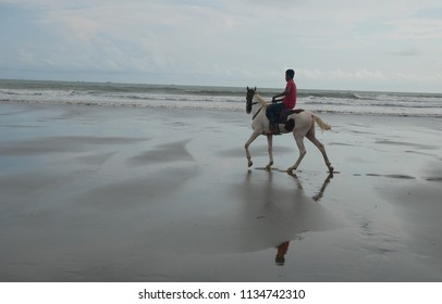 Cox's Bazar, Bangladesh,  - June 1, 2018, A  horse rider trots down the beach at Cox's Bazar, one of the longest uninterrupted beaches in the world.