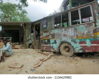 Cox's Bazar, Bangladesh - June 2, 2018. The rusted-out shell of a small bus occupies the roadside in an impoverished village between Cox's Bazar and the Rohingya refugee camps.