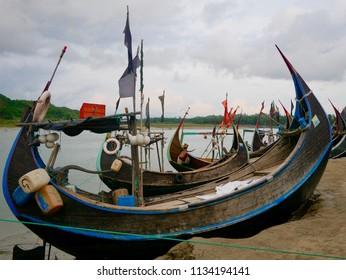 Cox's Bazar, Bangladesh - June 6, 2018 - Sampan-style fishing boats sit idle at low tide in a small fishing village south of Cox's Bazar.