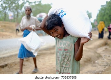 COX'S BAZAR, BANGLADESH: OCTOBER 10, 2017 - Children smile while bring heavy food packaging at the refugee distribution center in Ukiah. About hundreds of people line up for hours to pick up raw food.