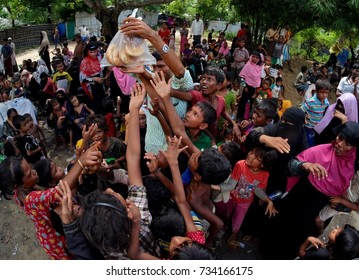 COX'S BAZAR, BANGLADESH: OCTOBER 8, 2017 - Rohingya people snatch bread when a man distributes food to hungry children near Dhakinpara.