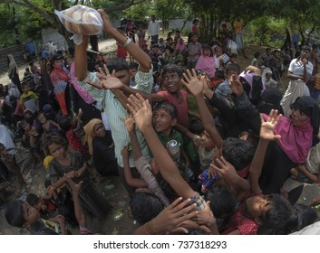 COX'S BAZAR, BANGLADESH: OCTOBER 8, 2017 - Rohingya children are starving when a man brings a pack of bread, they beg and ask for a piece of bread to eat near Dhakinpara