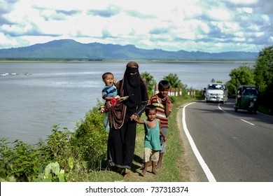 COX'S BAZAR, BANGLADESH: OCTOBER 9, 2017 - A mother brings her children away from the Myanmar state, The upheaval and the brutality of the Rohingyas forced them to run away near Teknaf, Bangladesh.