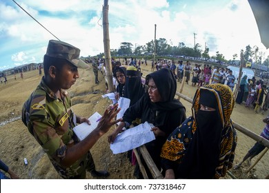 COX'S BAZAR, BANGLADESH: OCTOBER 9, 2017 - Bangladesh troops help some Rohingya migrants who are queuing for help. They ran away from Myanmar because of extreme violence against the Rohingyas.