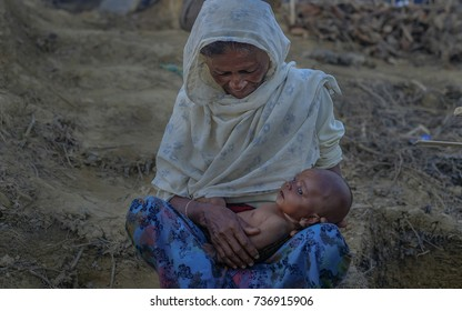 COX'S BAZAR, BANGLADESH: OCTOBER 9,2017 - A woman holds the baby while sitting and gazing at the baby in Balukhali, Ukiah.