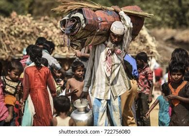 COX'S BAZAR, BANGLADESH - SEPTEMBER 25, 2017 : Members of Myanmar's Muslim Rohingya minority walk through a broken road in Kutupalong refugee camp near Cox's Bazar, Bangladesh.