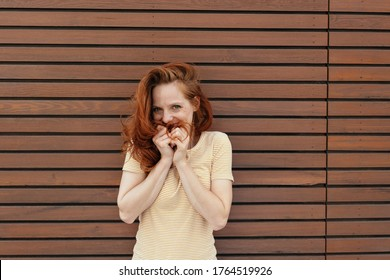 Coy or shy young woman looking at the camera as she giggles behind her hands against a timber style wall with copyspace