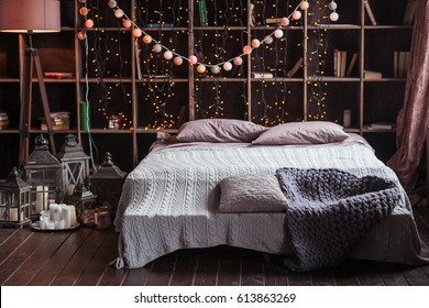 coziness, comfort, interior and holidays concept - cozy bedroom with bed and garland lights at home. A rack with books behind the bed. Candles, a lamp and a lamp stand near the bed. Plaid hand-knitted
