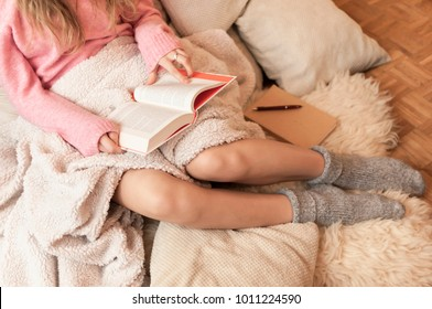 Coziness at home, girl hygge with book and blanket