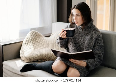 Coziness at home, inspirational concept. Woman enjoy hot chocolate and reading a book sitting at coach in cuddly modern room. Lazy weekend, cozy atmosphere, winter holidays