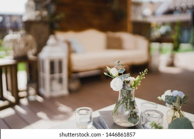 Coziness and style. Modern event design. Lounge and photo zone and european traditional wedding ceremony decoration outdoors in the restaurant before the reception.