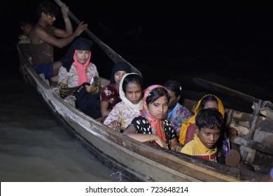 COZ'S BAZAR, BANGLADESH - SEPTEMBER 28, 2017: On a dark night Myanmar's minority Rohingya Muslim refugees disembark from a boat on the bank of Naf River at Shah Porir Deep, in Teknaf, Cox's Bazar,