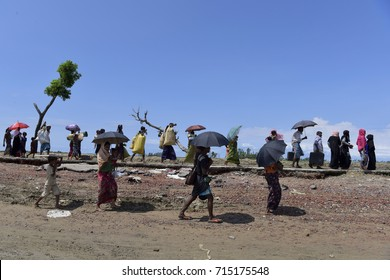 COZ'S BAZER, BANGLADESH - SEPTEMBER 11, 2017: Members of Myanmar's Muslim Rohingya minority walk through a broken road at Shah Porir Deep, at Teknaf in Cox's Bazer, Bangladesh on Seotember 11, 2017.