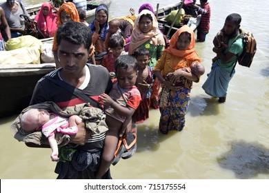 COZ'S BAZER, BANGLADESH - SEPTEMBER 11, 2017: Members of Myanmar's Muslim Rohingya minority walk through a broken road at Shah Porir Deep, at Teknaf in Cox's Bazer, Bangladesh on Seotember 11, 2017.
