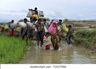 COZ'S BAZER, BANGLADESH - SEPTEMBER 11, 2017: Members of Myanmar's Muslim Rohingya minority walk through a broken road at Kanjir para, at Teknaf in Cox's Bazer, Bangladesh on September 11, 2017.