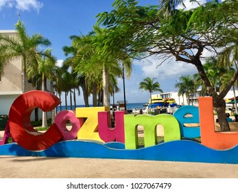 COZUMEL, MEXICO - DECEMBER 17, 2017: Colorful Cozumel sign on Cozumel Island with ferry harbor in the background.