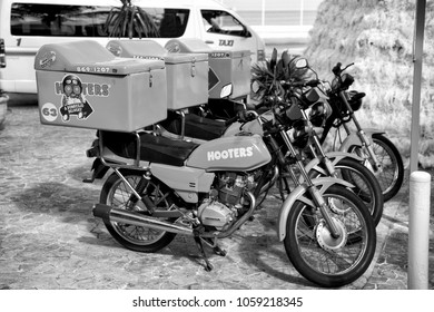 Cozumel, Mexico - December 24, 2015: hooters motorcycles of orange color parked on street outdoor. Food delivery service concept