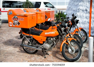 Cozumel, Mexico - December 24, 2015: hooters motorcycles of orange color parked on street outdoor. Food delivery service
