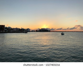 Cozumel, Mexico - February 4, 2019 - View of the pier of Cozumel at sunset with a boat at horizon.