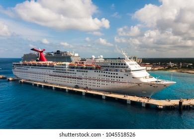 Cozumel, Mexico - JANUARY 12, 2018: Carnival Fantasy cruise ship docks at one of Puerta Maya peers in a sunny day, cloudy sky and clean blue sea water