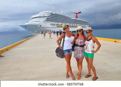 COZUMEL MEXICO - SEPTEMBER 9, 2013: Carnival cruise ship Liberty docks in the Cozumel port during one of the Western Caribbean cruises. Cruise passengers are taking a picture in front of cruise ship.