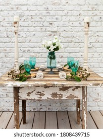 A cozy antique farmhouse table for 4 with a vibrant pop of colo, vintage candlesticks and greenery against a distressed white brick wall.
