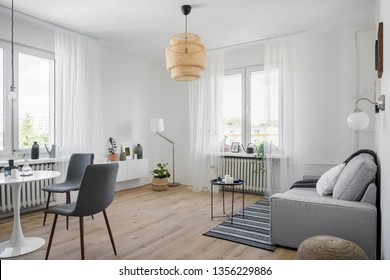 Cozy apartment interior with sofa, round table and chairs