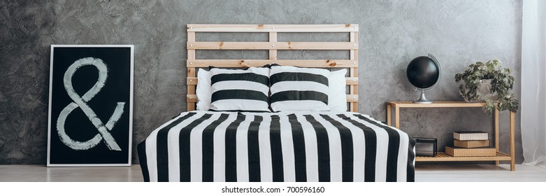 Cozy apartment with stylish black and white decor, striped bedding, poster and dark gray wall