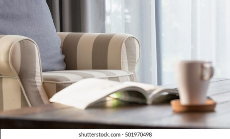 Cozy armchair with gray pillow in a bright room with white curtain , wooden tea table  with an opened book and a cup of coffee.