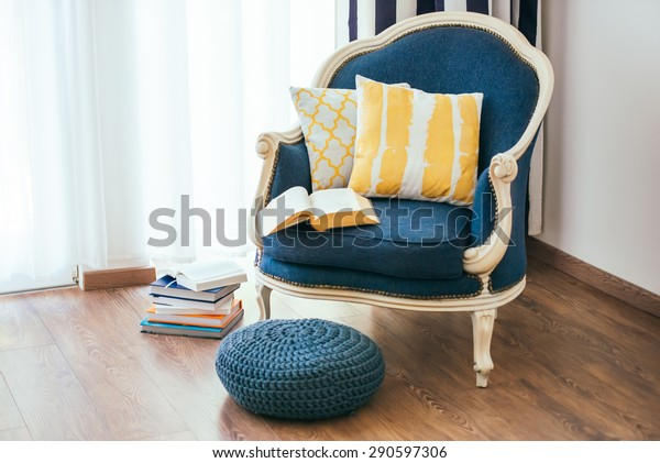 Cozy armchair with open book and decorative pillows. Interior and home decor concept