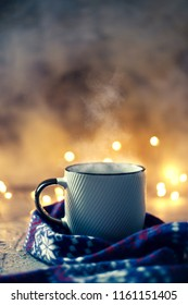 Cozy atmosphere with winter coffee or tea mug with steam covered with wool scarf over bokeh lights