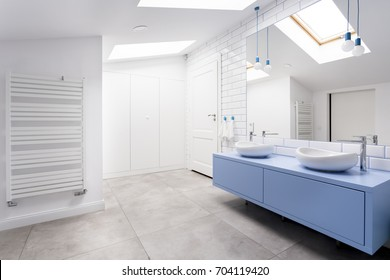 Cozy attic bathroom with grey floor, blue washbasin cabinet and heater