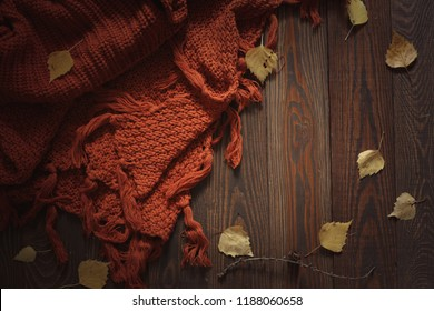 Cozy autumn background with knitted sweater scarf on a wooden background, with yellow birch leaves, concept autumn season,