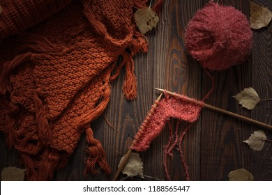 Cozy autumn background with knitted sweater scarf and ball with knitting wood needles, concept handicraft and fall season